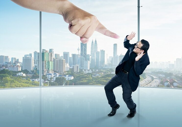 A scared businessman full-height in a scare pose and a giant hand pointing at him, on the office background. Business and management. Employment issues. Getting fired. Being told off.